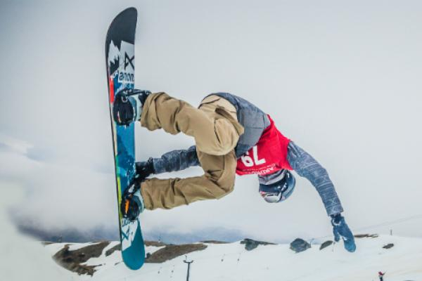 A snowboarder competing in the halfpipe